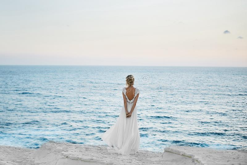 Beautiful young blonde model girl in white dress stands back and looks at the sea stock photography