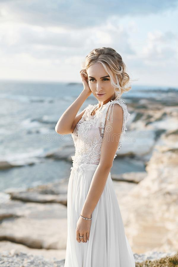 Beautiful young blonde model woman with nude makeup in a fashionable wedding dress walking at the sea coast at Cyprus stock photos
