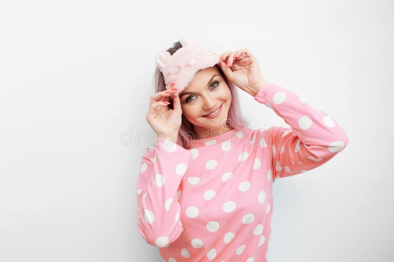 Beautiful young blonde in pink pajamas and a sleep mask