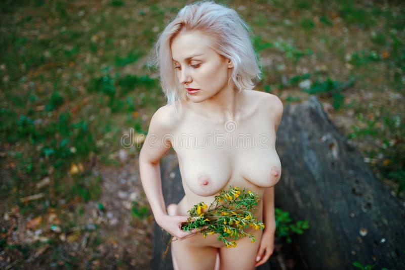 Beautiful young blonde with short hair with yellow flowers in hand posing kneeling co mpletely naked royalty free stock photography