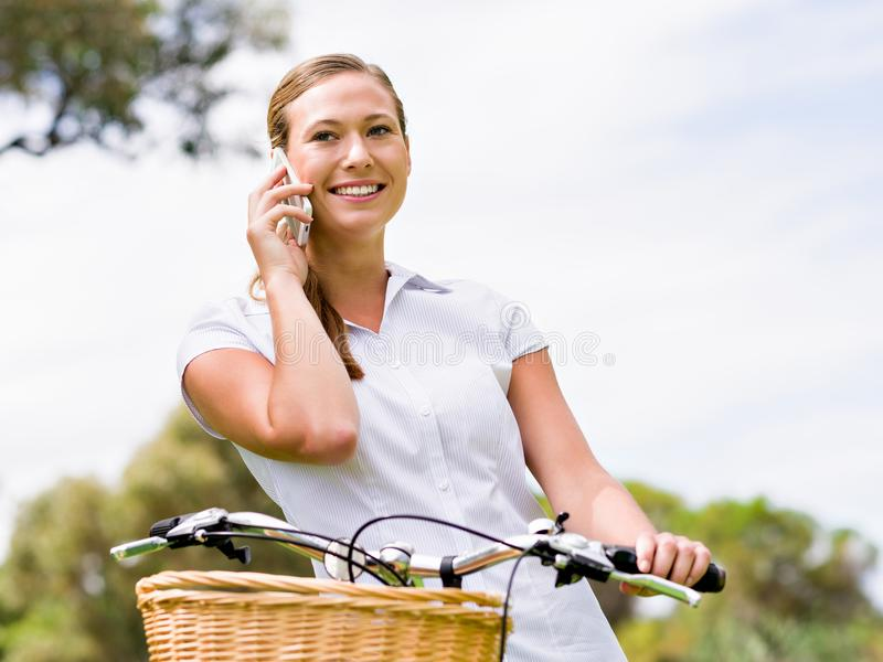 Beautiful young blonde woman with bike in park talking over phone royalty free stock photo