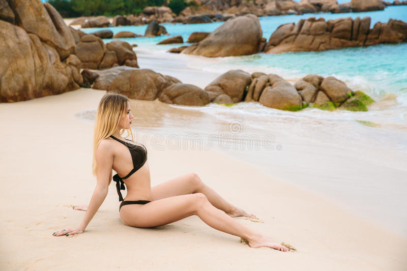 Beautiful young blonde woman in black bikini posing. sitting on the beach. model portrait with perfect body stock photos