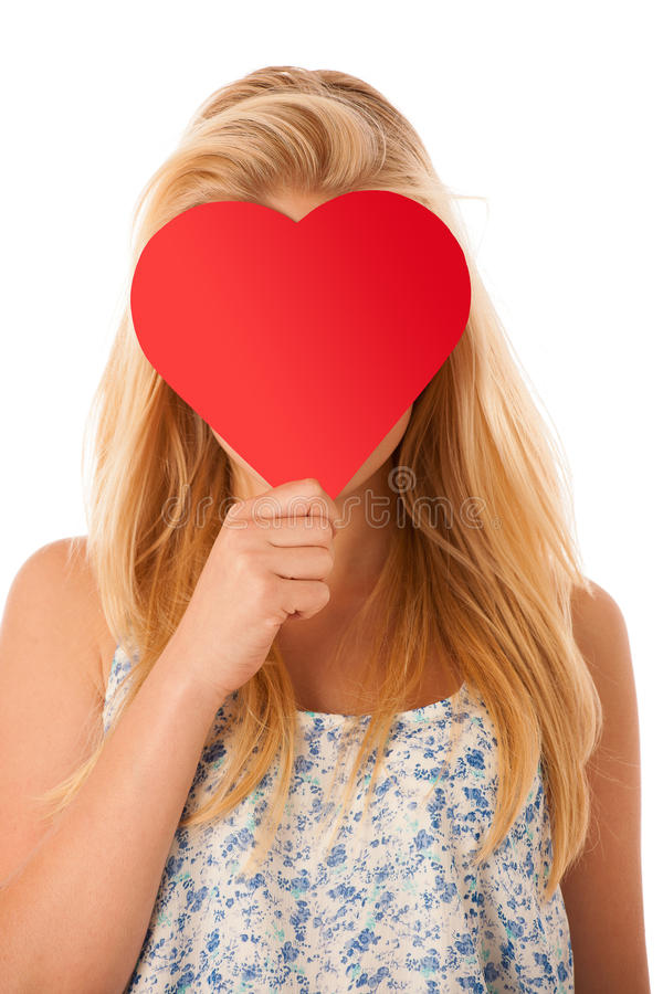 Beautiful young blonde woman with blue eyes holding red hart ban royalty free stock photography