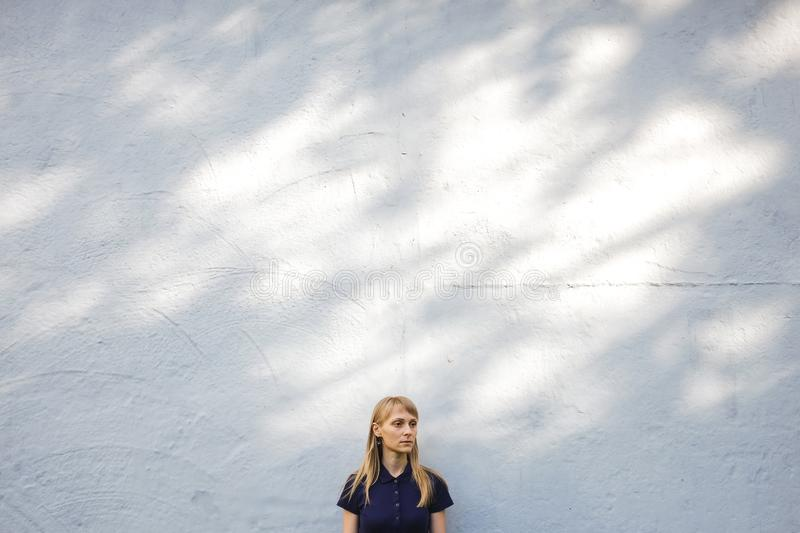 Beautiful young blonde woman in blue Polo shirt standing at white stone wall outdoors. A serious girl with long hair looks away, royalty free stock images