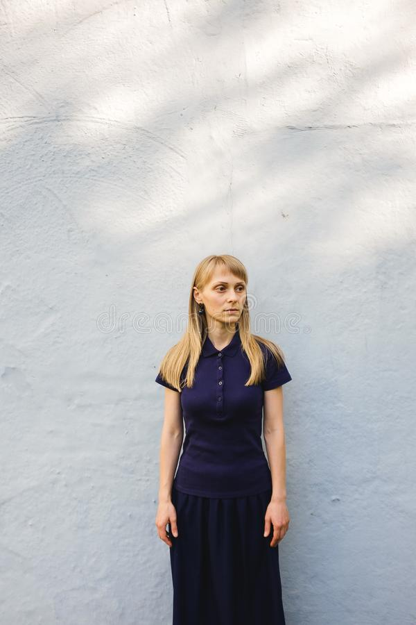Beautiful young blonde woman in blue Polo shirt standing at white stone wall outdoors. A serious girl with long hair looks away, stock photography