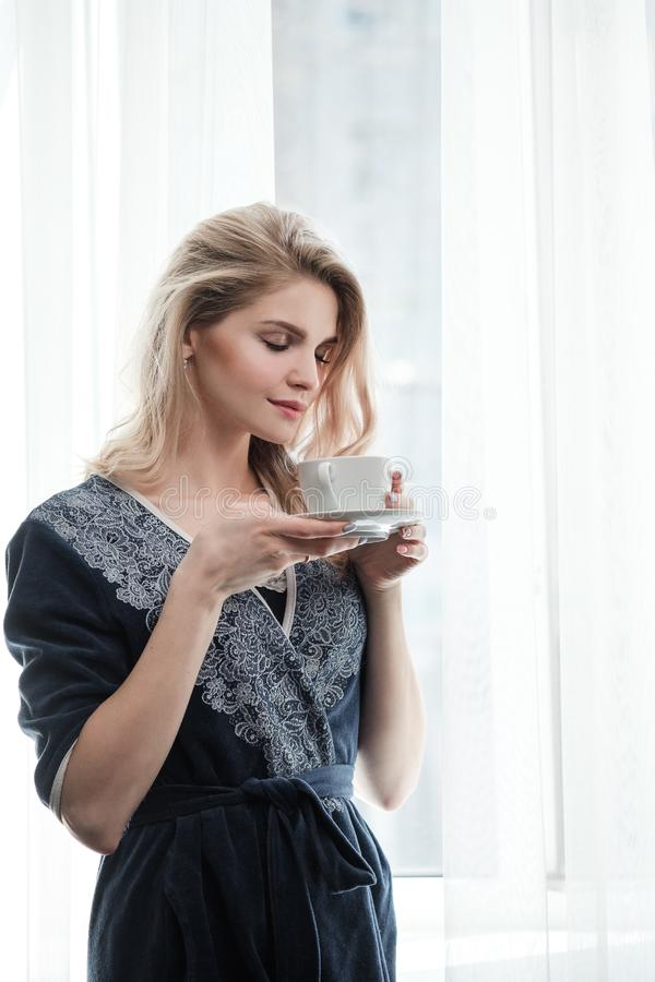Beautiful young blonde woman in a blue robe by the window. Drinks coffee or tea from a white cup with a saucer. Morning. Sunshine, bedroom window. Close-up stock photo