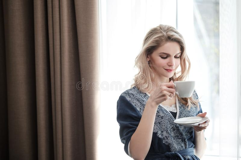 Beautiful young blonde woman in a blue robe by the window. Drinks coffee or tea from a white cup with a saucer. Morning. Sunshine, bedroom window. Close-up stock images
