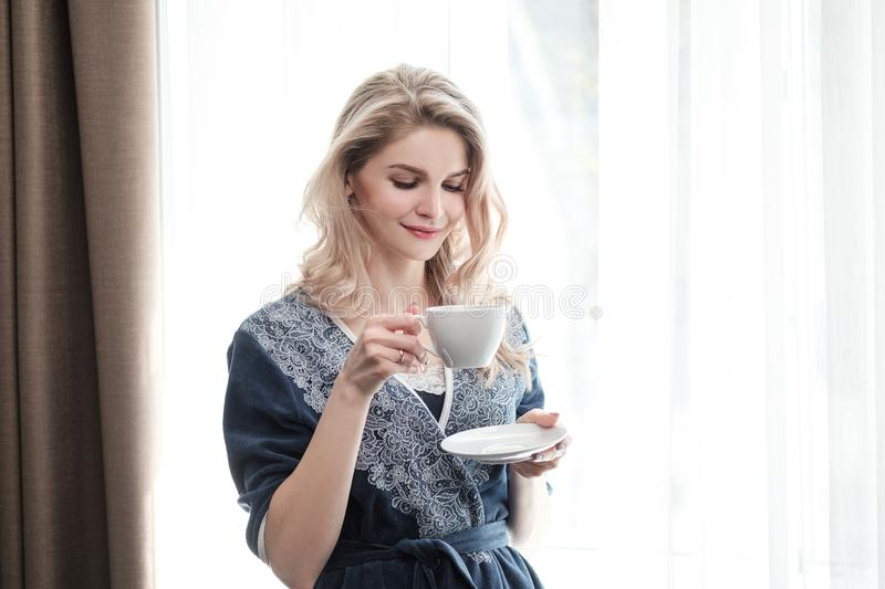 Beautiful young blonde woman in a blue robe by the window. Drinks coffee or tea from a white cup with a saucer. Morning royalty free stock photo