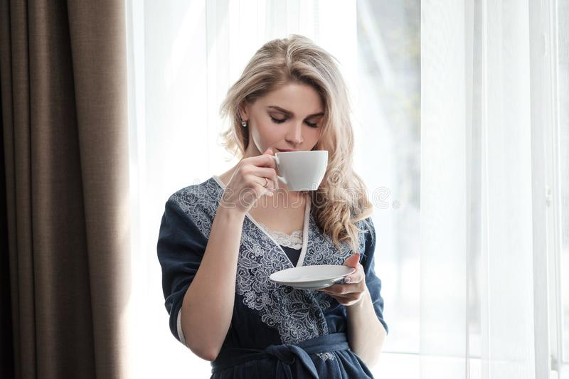 Beautiful young blonde woman in a blue robe by the window. Drinks coffee or tea from a white cup with a saucer. Morning stock image