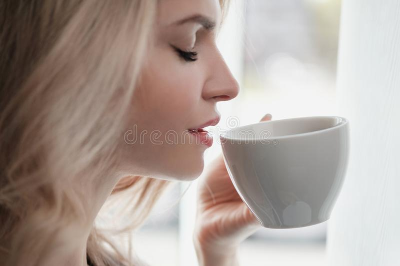 Beautiful young blonde woman in a blue robe by the window. Drinks coffee or tea from a white cup with a saucer. Morning stock images
