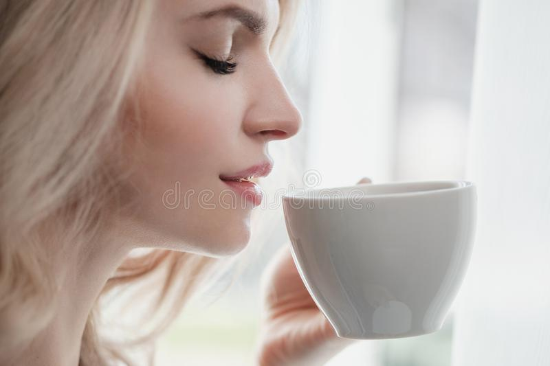 Beautiful young blonde woman in a blue robe by the window. Drinks coffee or tea from a white cup with a saucer. Morning stock photo