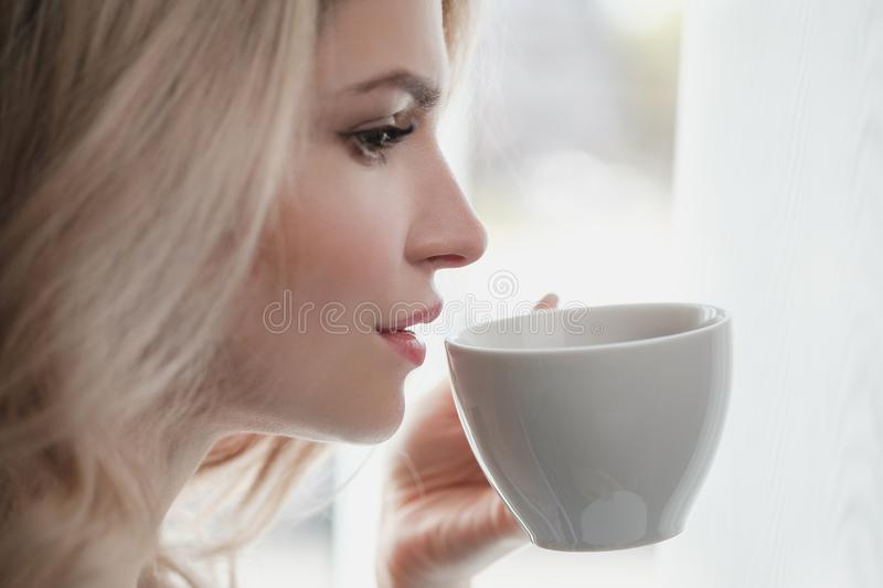 Beautiful young blonde woman in a blue robe by the window. Drinks coffee or tea from a white cup with a saucer. Morning stock photography