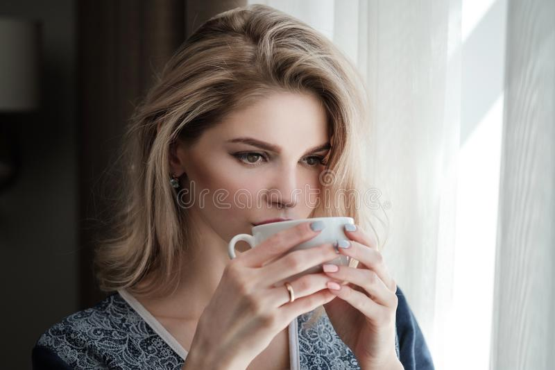 Beautiful young blonde woman in a blue robe by the window. Drinks coffee or tea from a white cup with a saucer. Morning royalty free stock photos