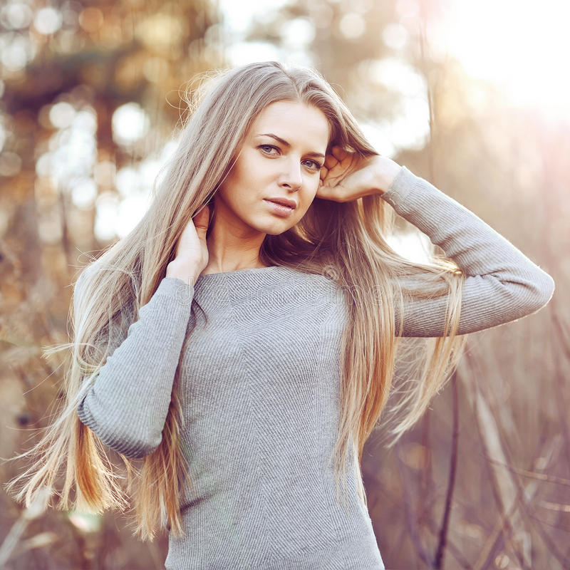 Beautiful young blonde woman with chic long hair royalty free stock images