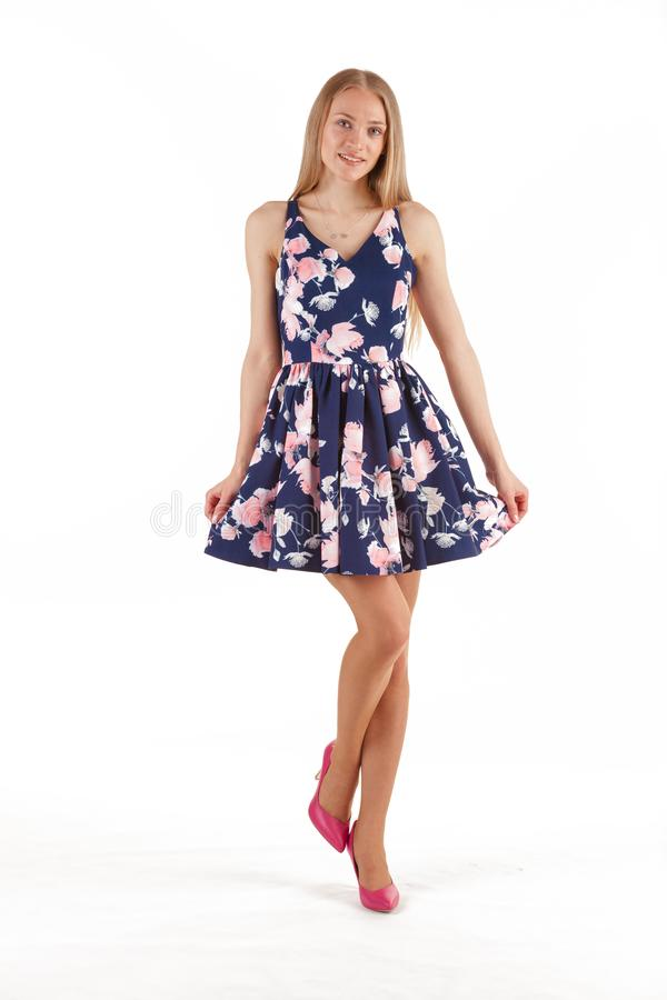 Beautiful young blonde woman in dark blue dress with floral print isolated on white background stock photos