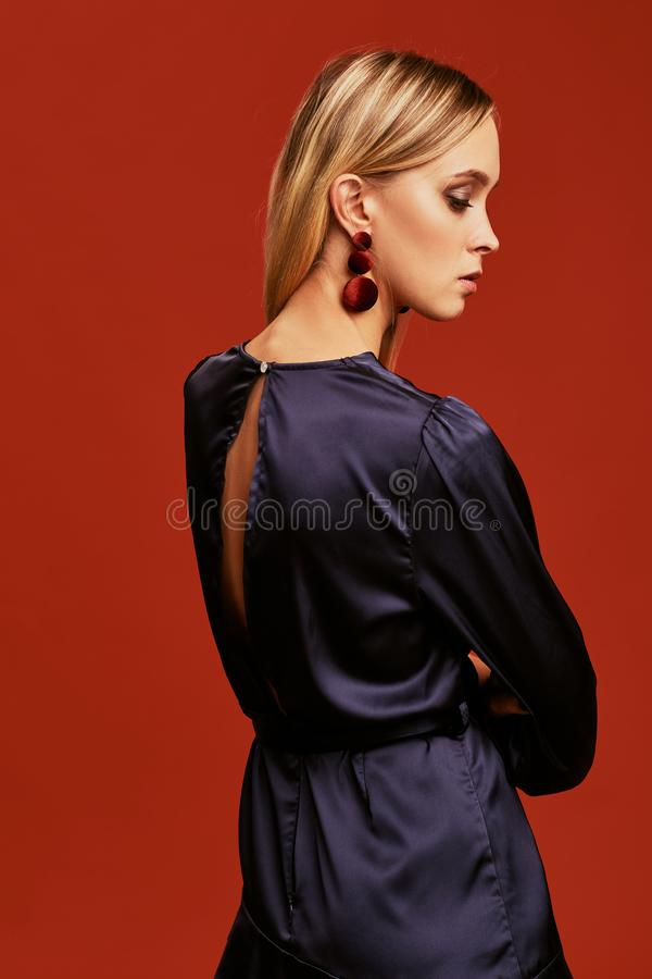 Beautiful young blonde woman in elegant black cocktail dress with cutout is posing for camera. stock photo
