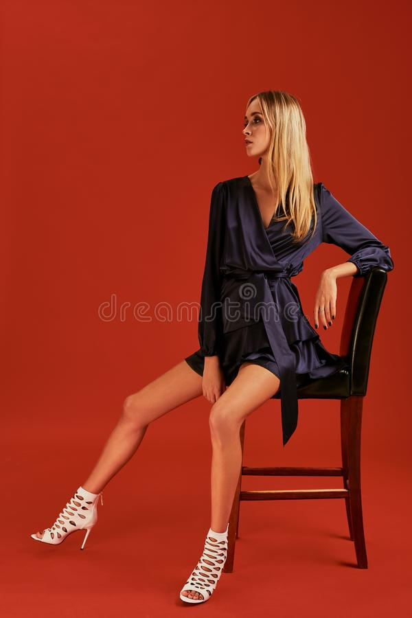 Beautiful young blonde woman in elegant black cocktail dress is posing for camera leaning on a chair stock photos