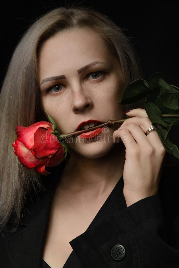 Beautiful young blonde woman with freckles holding a red rose in her mouth royalty free stock photography