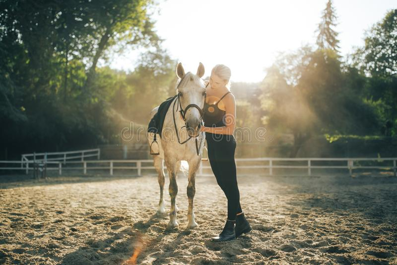 Beautiful young blonde woman with a horse royalty free stock photography