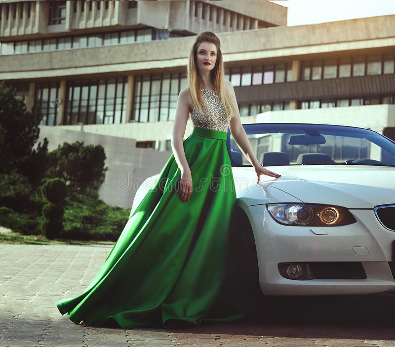 A beautiful young blonde woman in a luxurious green long evening dress is standing near a cabriolet car. royalty free stock image