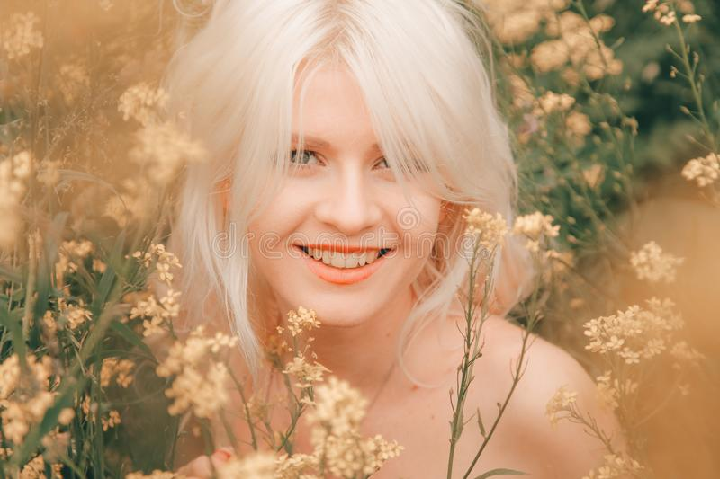 Beautiful young blonde woman on the meadow with yellow flowers on a warm summer day royalty free stock photos