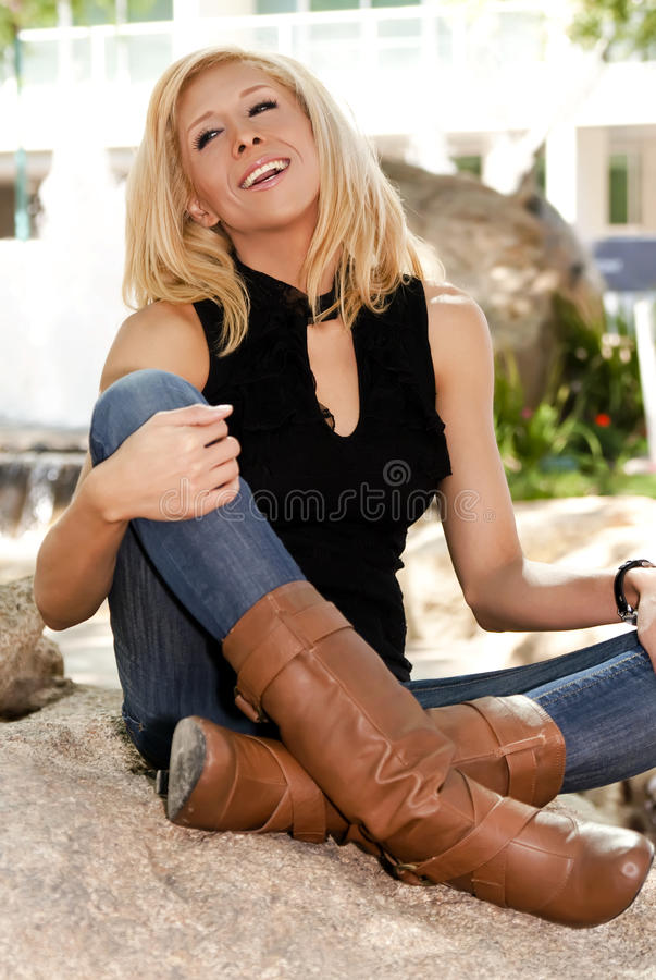 Beautiful young blonde woman in the park royalty free stock image