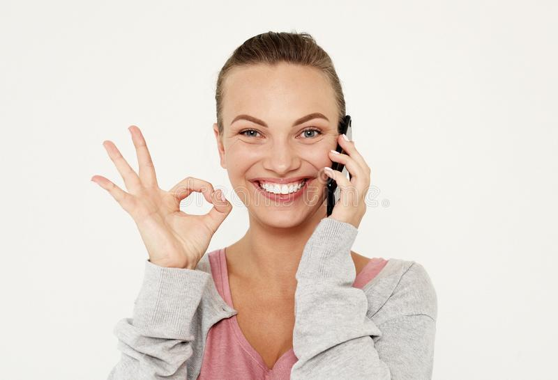 A beautiful young blonde woman picks up the news on the phone and is surprised. Great news! Over white background. stock photos