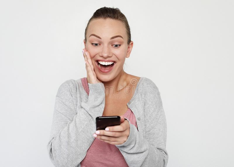 A beautiful young blonde woman picks up the news on the phone and is surprised. Great news! Over white background. stock photography