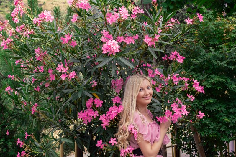 Beautiful young blonde woman in a pink dress stands posing outdoors near a bush with flowers. stock photos