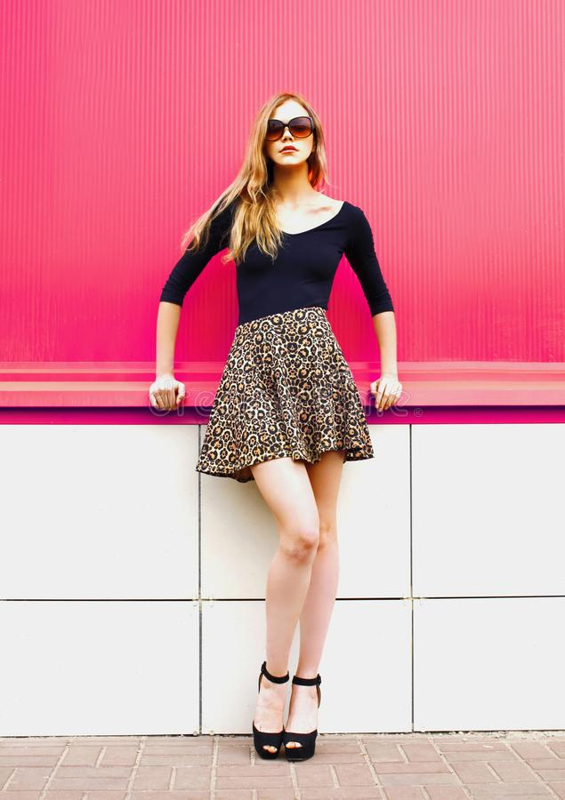Beautiful young blonde woman posing in leopard skirt and sunglasses on city street over colorful pink wall royalty free stock photo