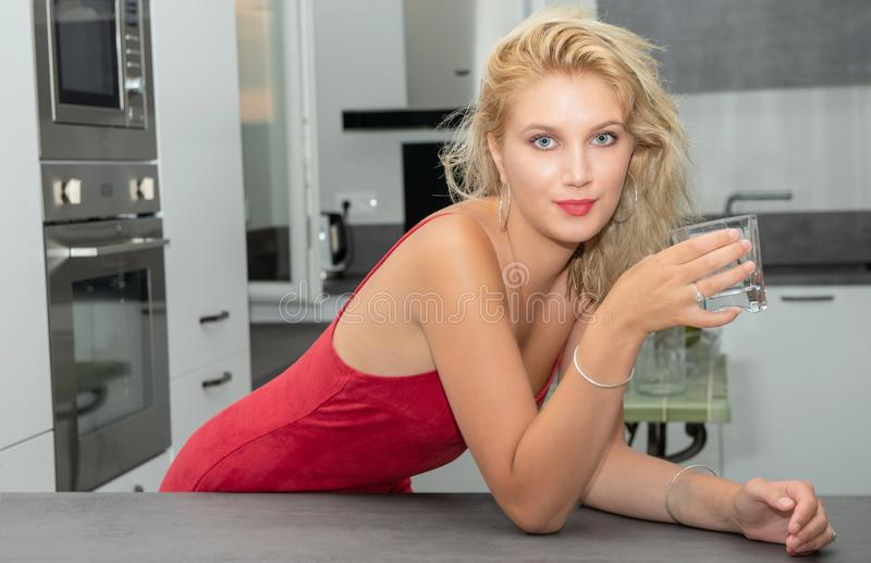 Beautiful young blonde woman with red dress drinking water stock images