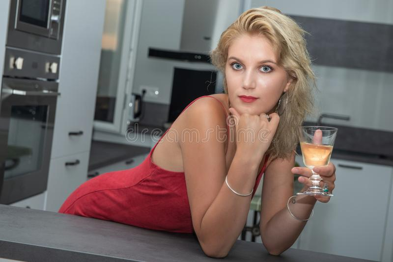 Beautiful young blonde woman with red dress drinking white wine in the kitchen royalty free stock photos
