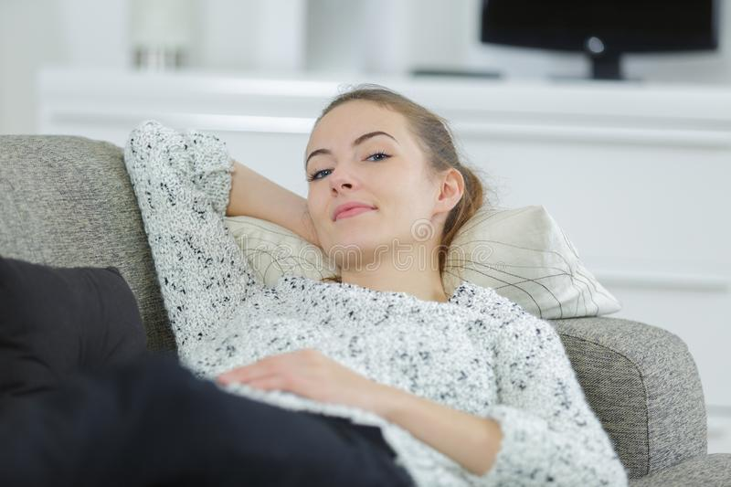 Beautiful young blonde woman relaxing on sofa royalty free stock images