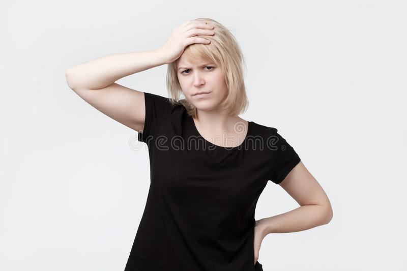 Beautiful young blonde woman scratching the head. Trying to remember hometask stock image