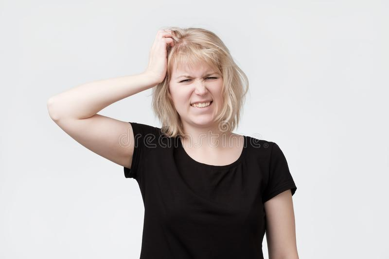 Beautiful young blonde woman scratching the head. Trying to remember hometask stock photography