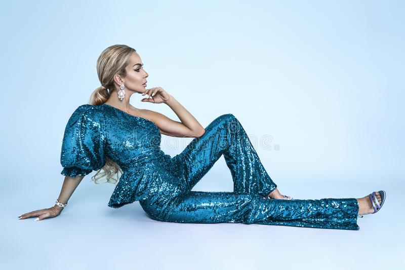 Beautiful young blonde woman in sexy sequin outfit. Carnival disco fashion woman. Party glamour photo, silver confetti, disco ball royalty free stock image