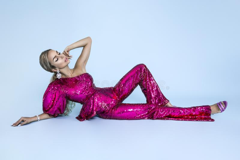 Beautiful young blonde woman in sexy sequin outfit. Carnival disco fashion woman. Party glamour photo, silver confetti, disco ball royalty free stock photography
