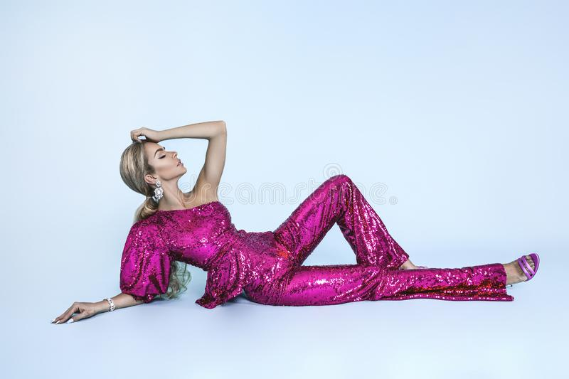 Beautiful young blonde woman in sexy sequin outfit. Carnival disco fashion woman. Party glamour photo, silver confetti, disco ball royalty free stock photo