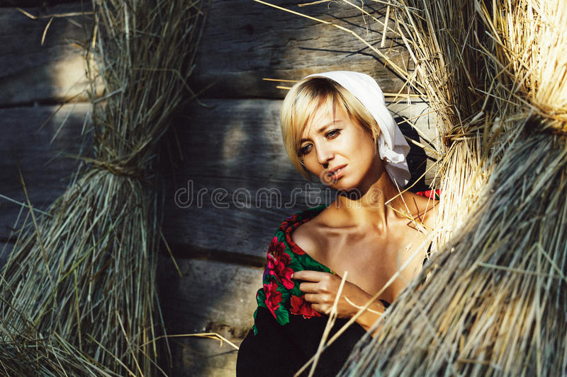 Beautiful young blonde woman sitting near the hay in the yard in rural areas stock photos