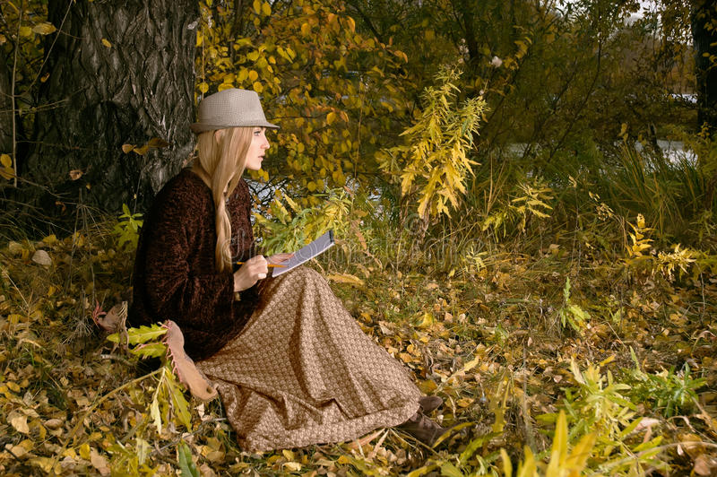Beautiful young blonde woman sitting outdoors in last sunbeams at autumn sunset paint a sketch in notepad royalty free stock photography