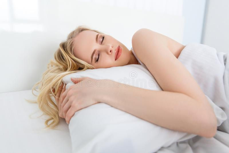 beautiful young blonde woman sleeping on white pillow stock photography