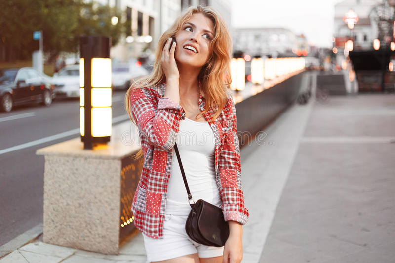 Beautiful young blonde woman speaks with boyfriend by a phone on the street city. royalty free stock photo