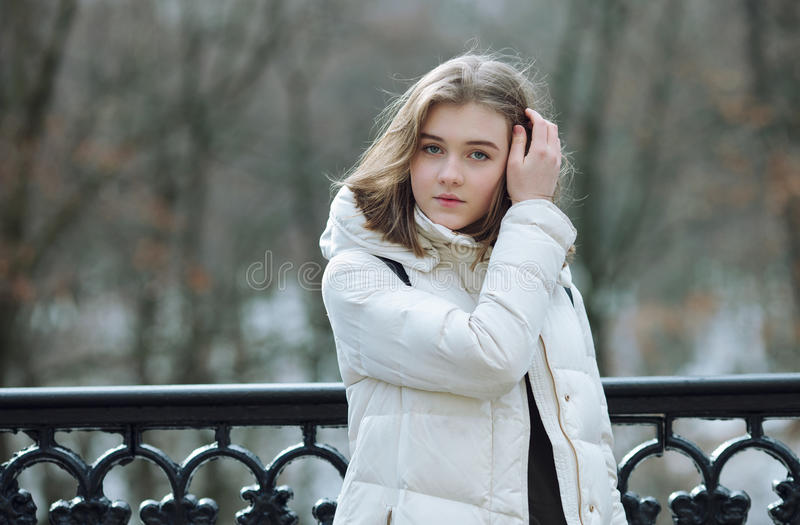 Beautiful young blonde woman standing on the spring city park in warm clothes. Cold season lifestyle freshness concept. Beautiful young blonde lady standing on royalty free stock photos