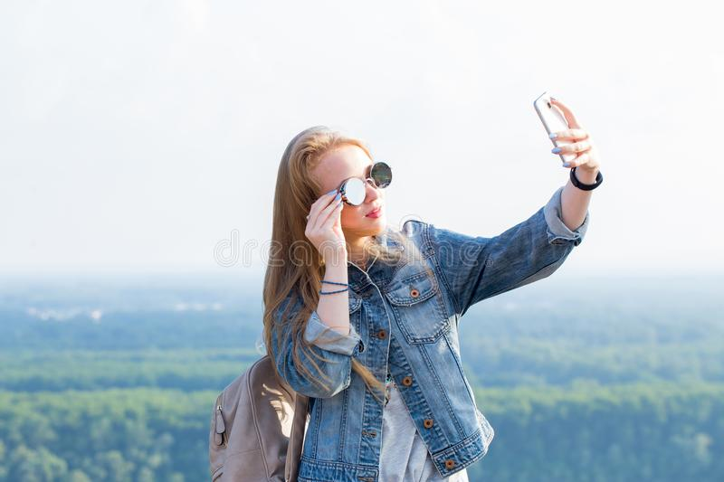 Beautiful young blonde woman in sunglasses takes a selfie against the landscape, nature in the mountains. Modern technology, travel, summer, lifestyle concepts royalty free stock photography