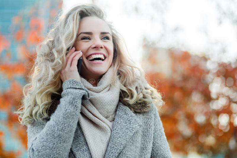 Beautiful young blonde woman talking on phone and laughing outdoors royalty free stock images
