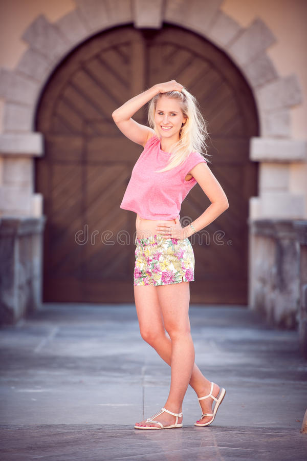 Beautiful young blonde woman on a walk around the city stock photo