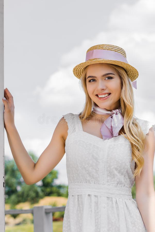 beautiful young blonde woman in wicker hat and tender dress smiling stock photo