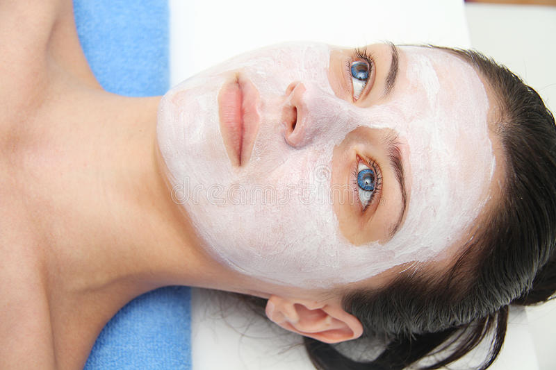 Beautiful young blue eye woman with clay facial mask. Beautiful young woman with clay facial mask stock image
