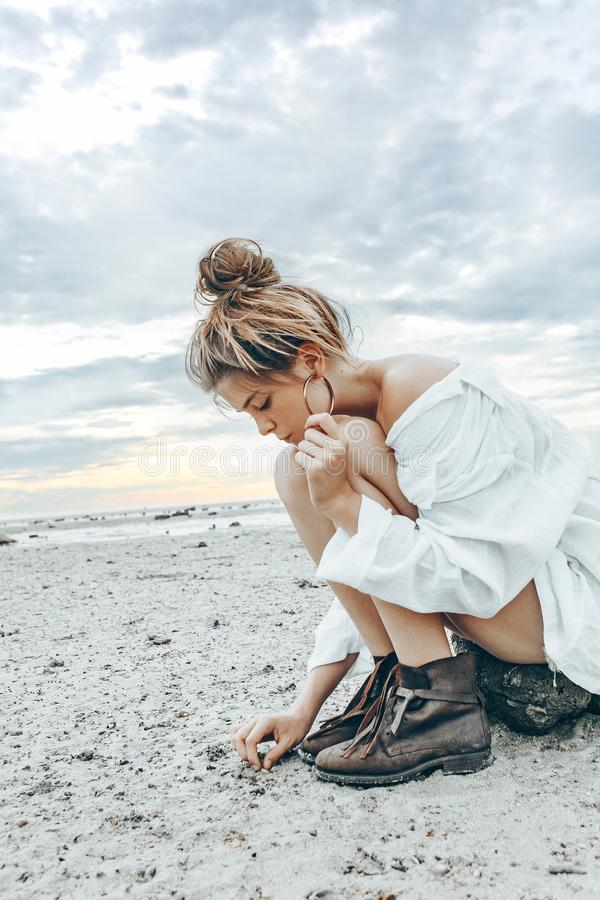 Beautiful young boho style girl on the beach at sunset. young na. Tural fashion model royalty free stock images