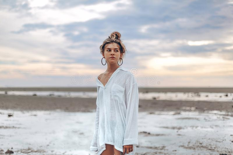 Beautiful young boho style girl on the beach at sunset. young na stock image